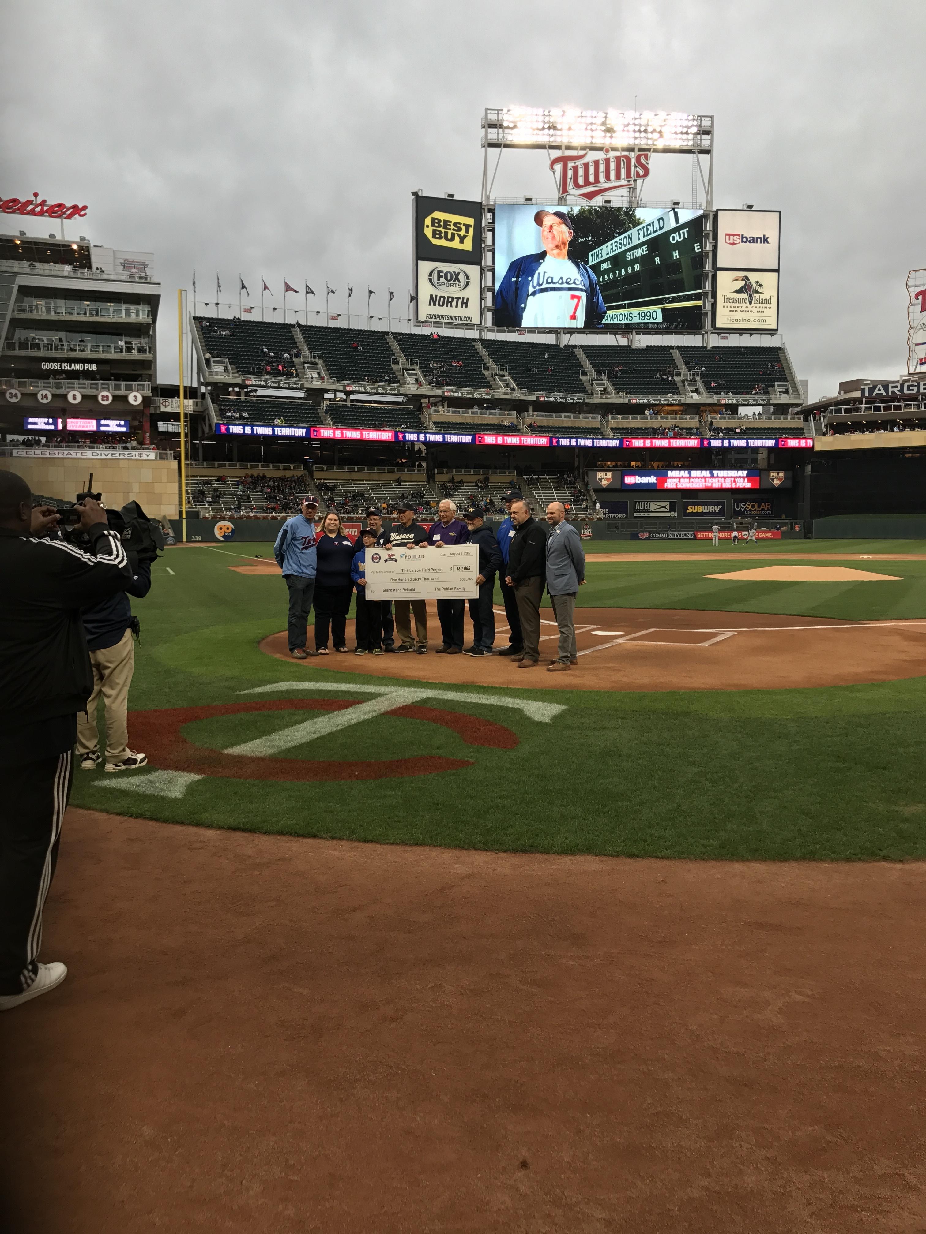 Group Holding Giant Check for Photo on Twins Baseball Diamond